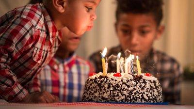 Menino pequeno assoprando velas em cima de um bolo, e um menino mais velho ao seu lado olha a cena.