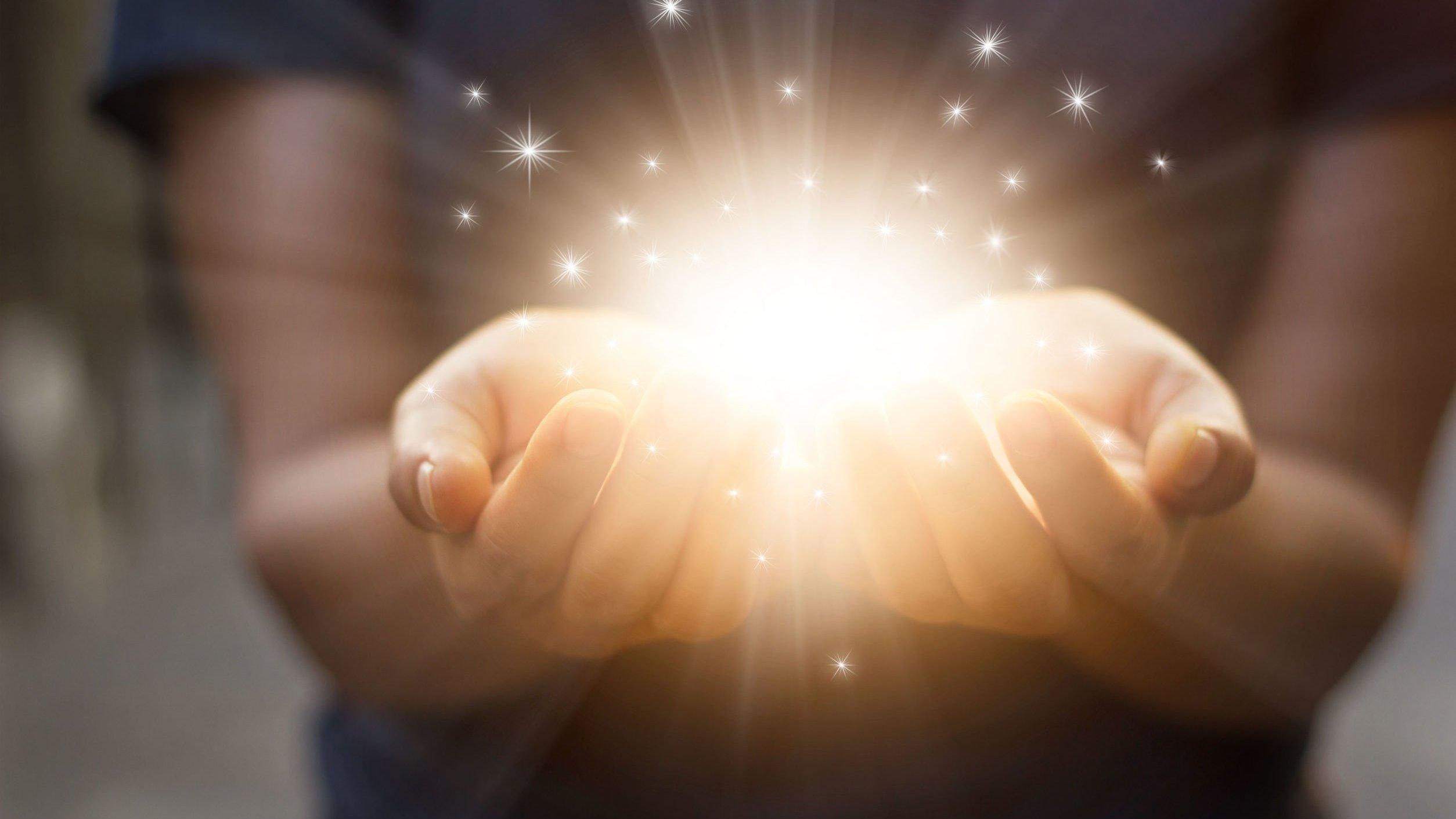Mãos da mesma pessoa, curvadas com a palma virada para cima, juntas. Dentro delas, uma bola de luz com pequenos pontos ao redor.