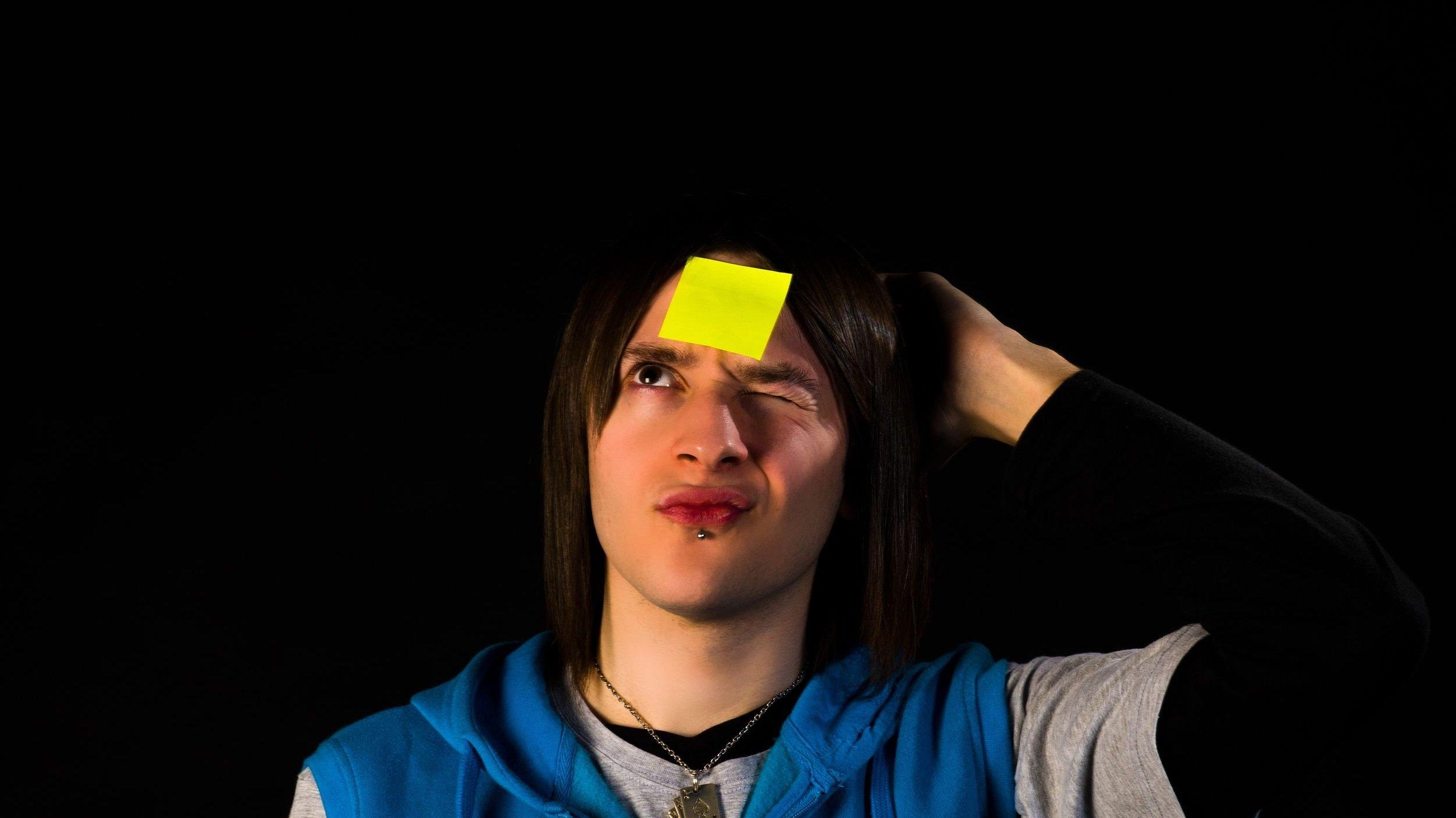 Foto de pessoa distraída com post it colado na testa