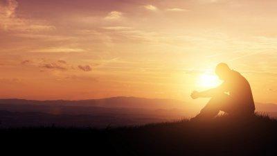 Homem rezando sob o nascer do sol.