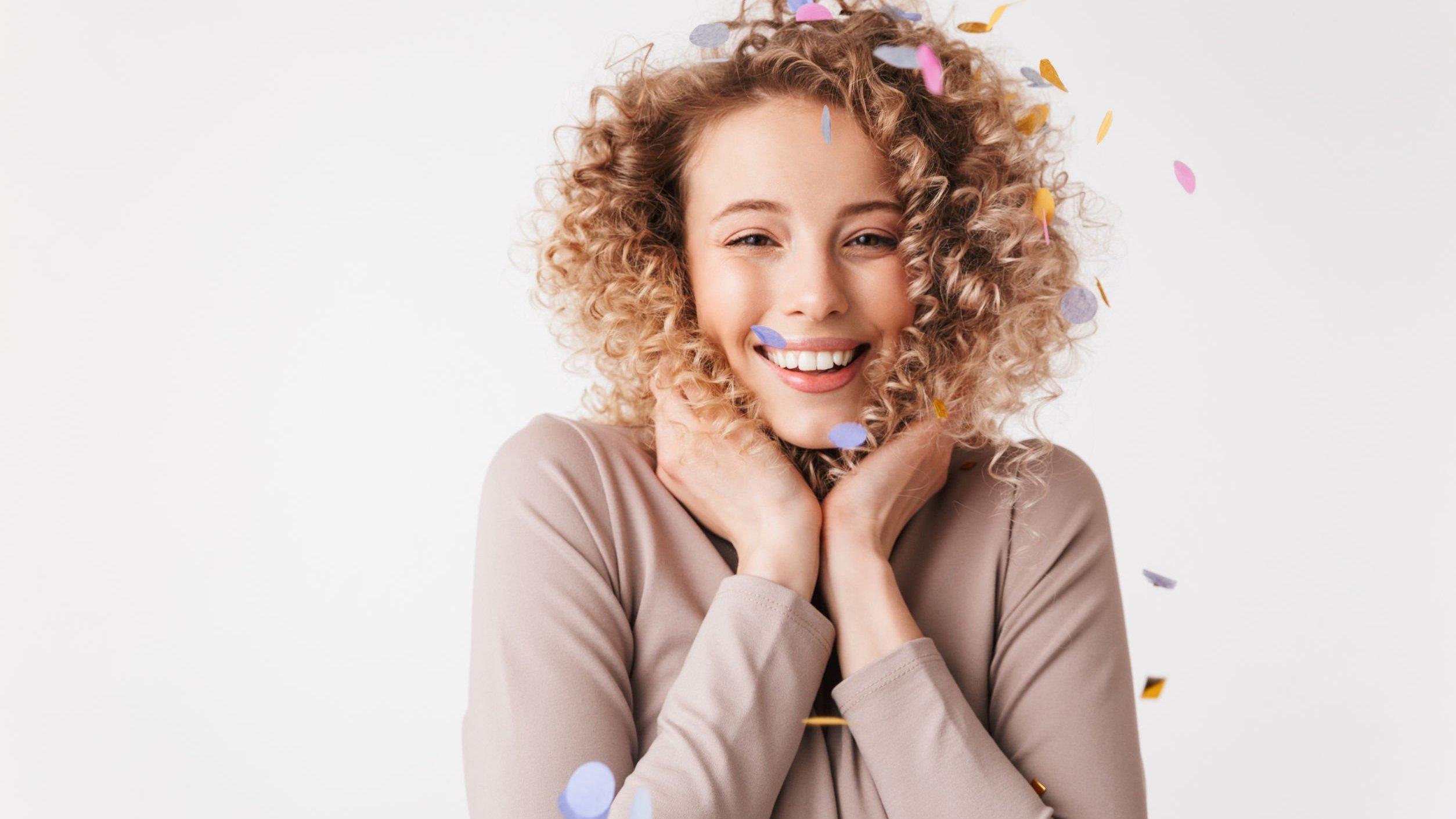 Mulher sorrindo com confete colorido caindo em sua cabeça