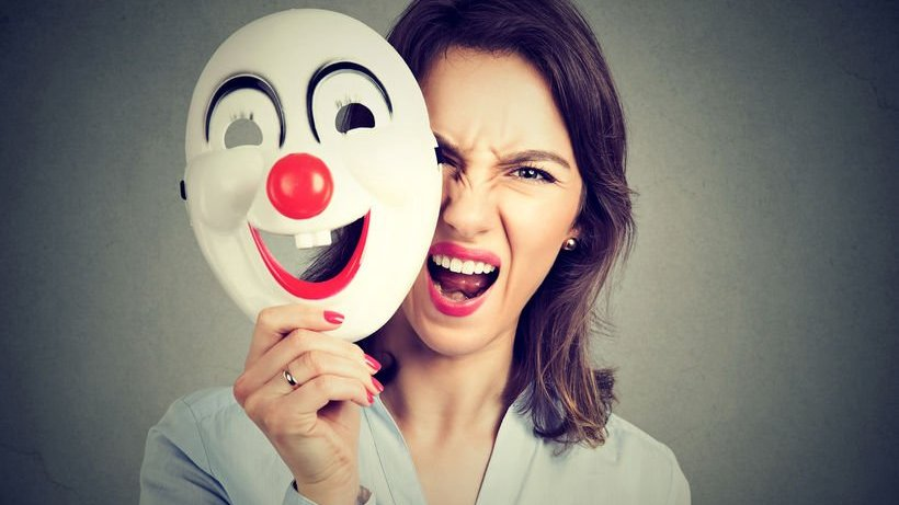 Mulher com expressão de fúria segurando uma máscara.