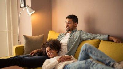 Casal no sofá assistindo TV