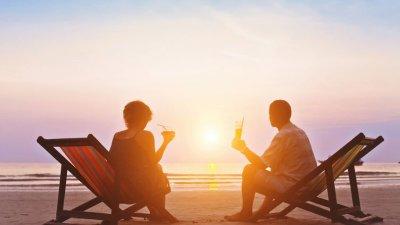 Casal na praia observando o pôr do sol