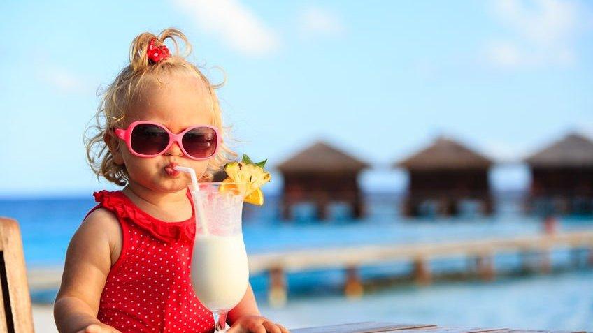 Criança na praia bebendo um suco
