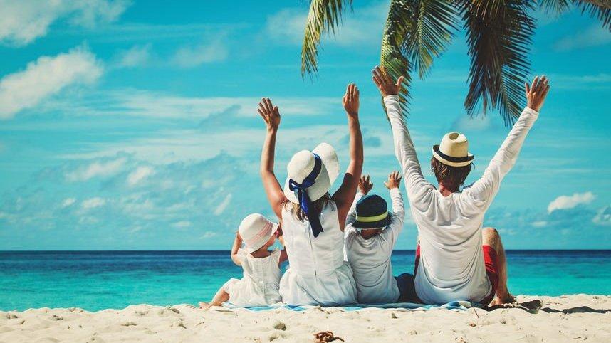 Família sentada em frente ao mar, com os braços para o alto.