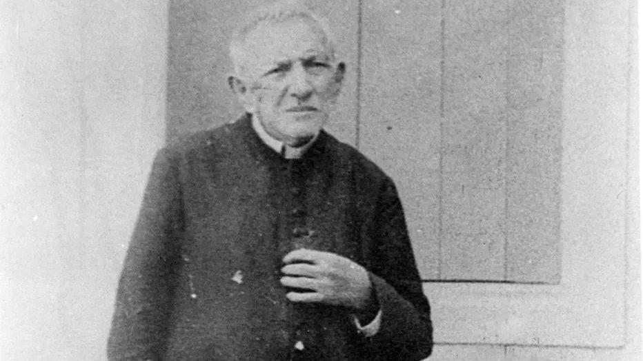 Padre Cícero em frente a porta de madeira.