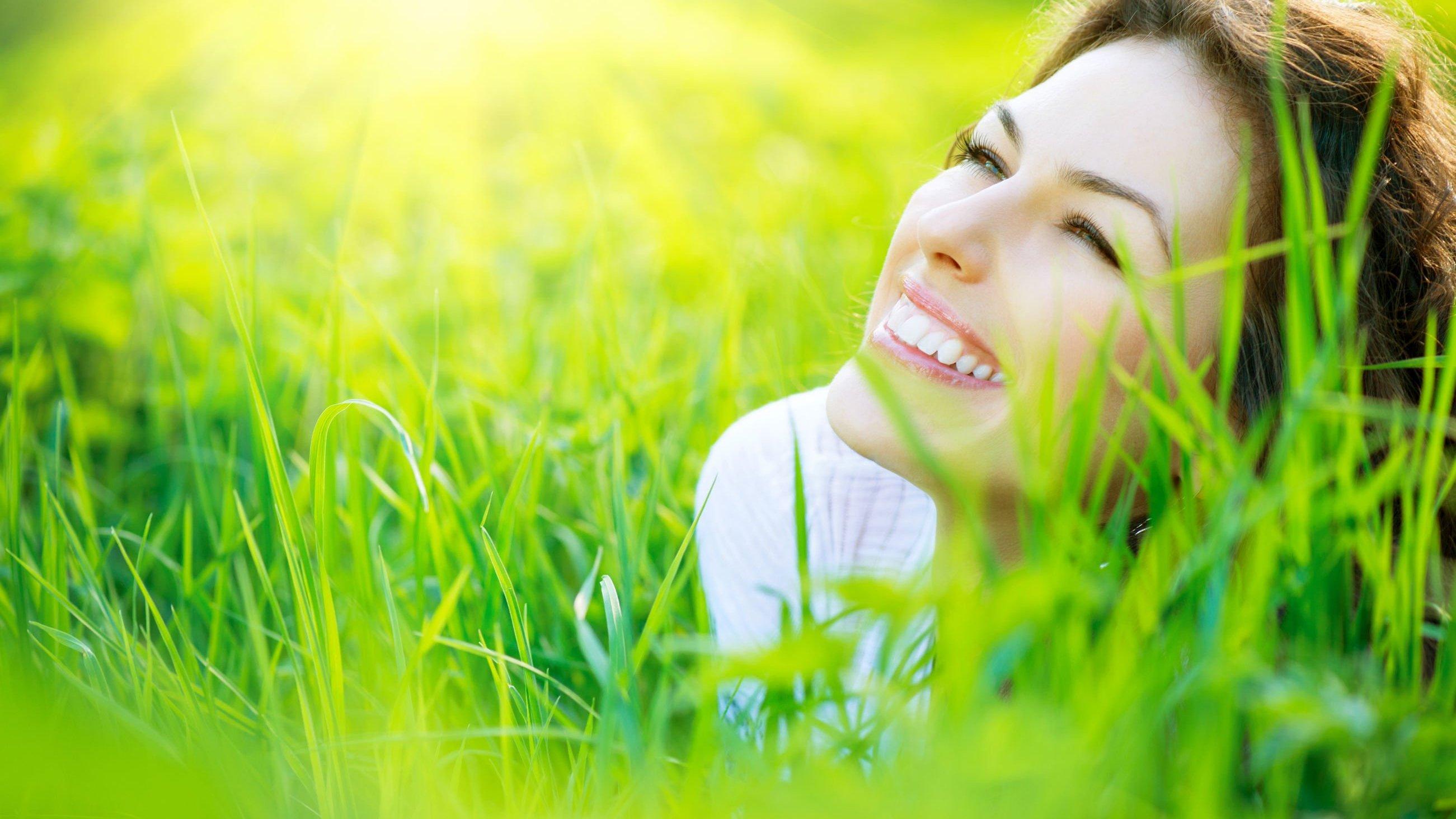 Mulher deita de bruços na grama e sorrindo.