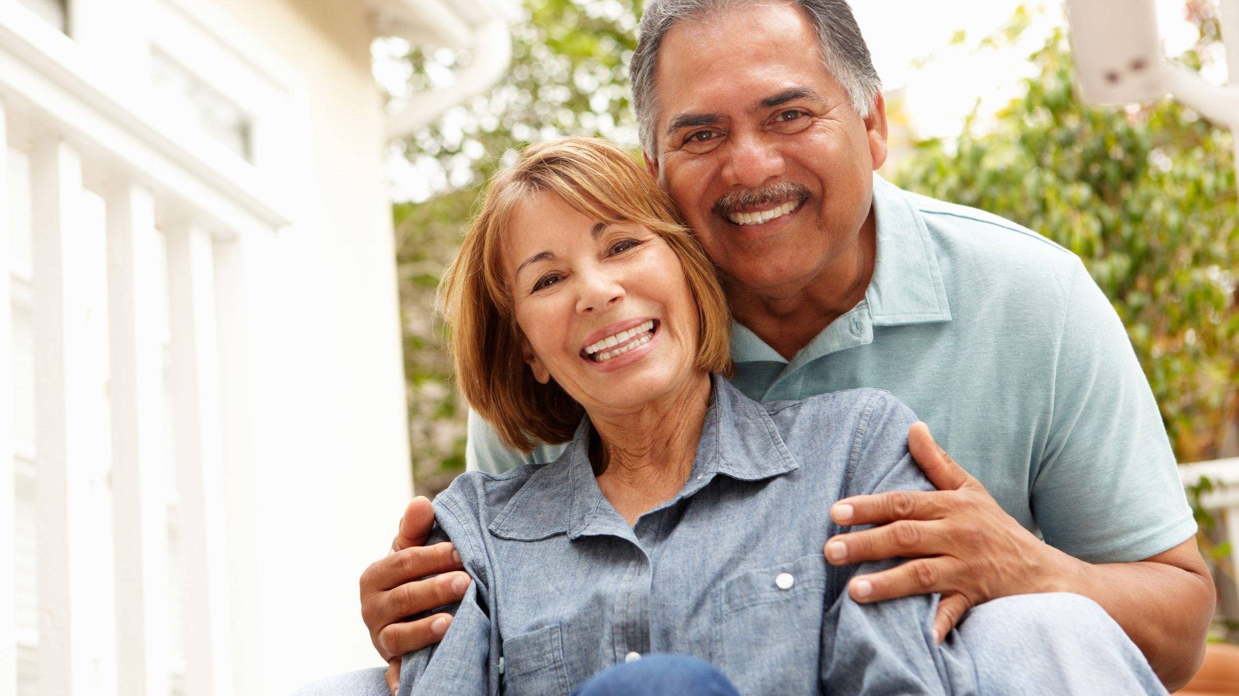 Casal sorrindo abraçados sentados no sofá