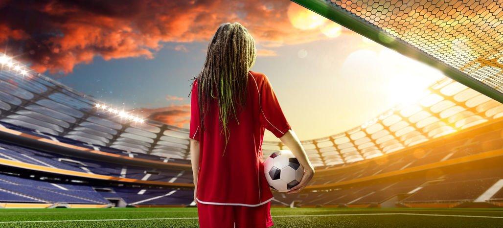 Menina em um estádio de futebol com a bola na mão