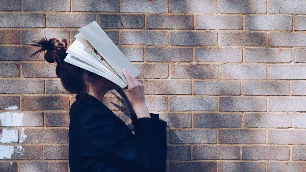 Mulher segurando um livro aberto sobre seu rosto.