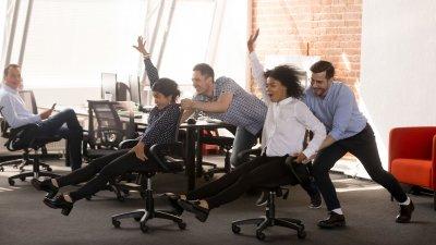 Quatro pessoas fazendo corrida de cadeira com cadeiras de rodas do escritório. Dois homens empurram, e duas mulheres estão sentadas nas cadeiras.