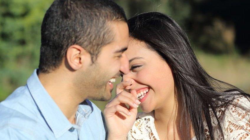 Casal sorrindo um para o outro