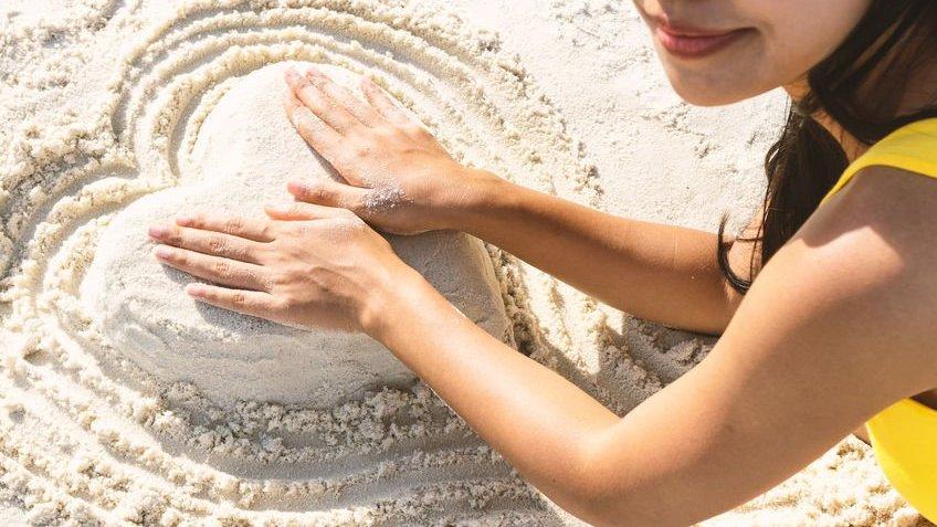 Mulher fazendo coração de areia