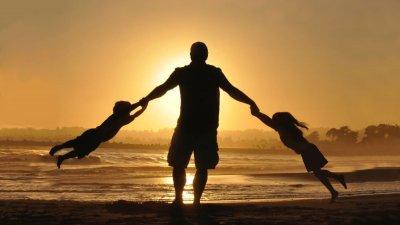 Silhueta de um pai rodando duas crianças, uma segurando em cada mão.