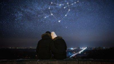 Casal sentados olhando um céu estrelado