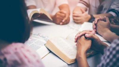 Mãos sobre Bíblias