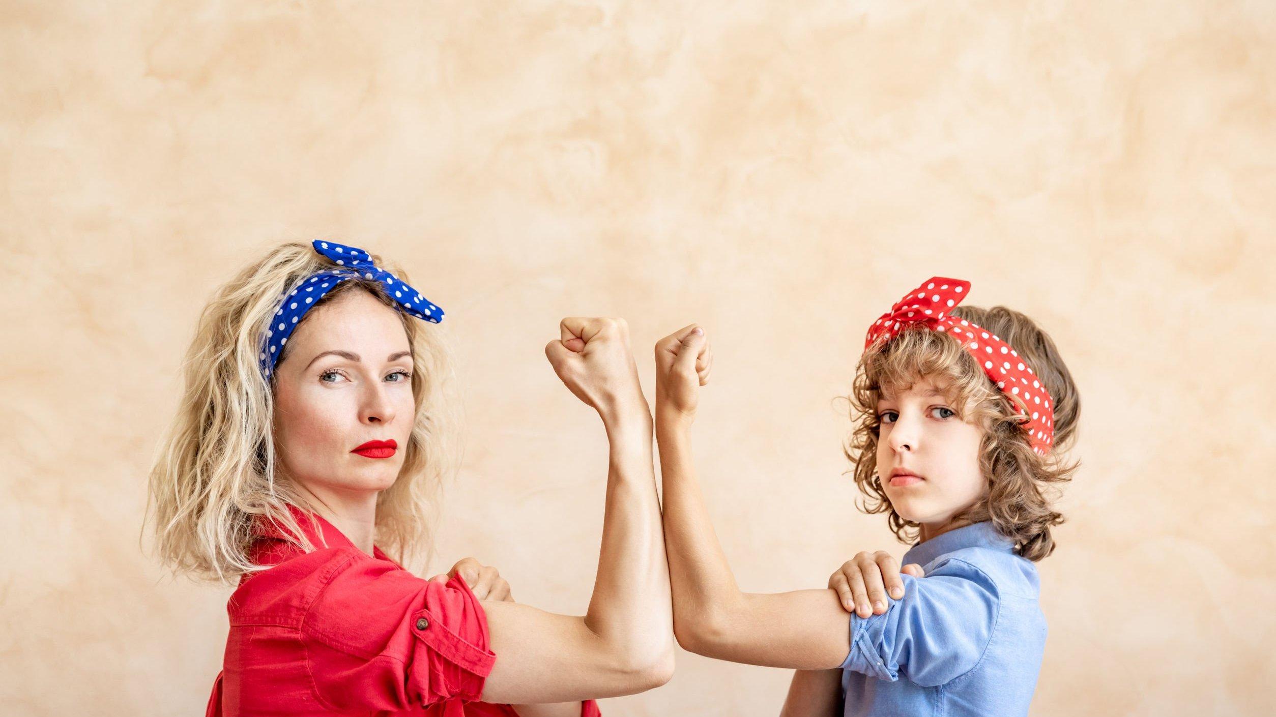 Mulher e criança com bandana na cabeça e com os braços simbolizando força