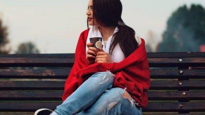Mulher sentada em um banco de madeira olhando para o lado pensativa segurando um copo de café