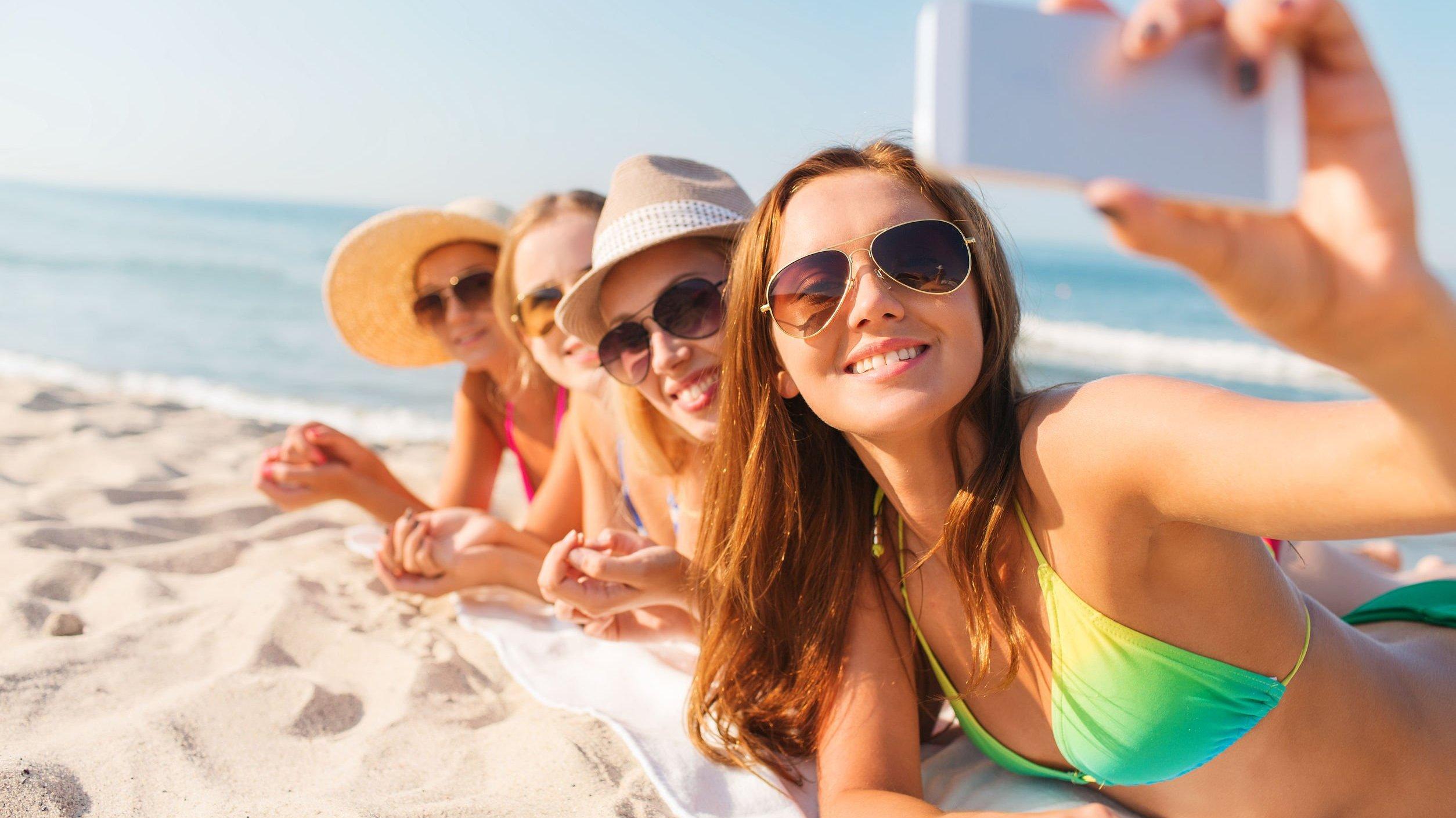 Foto de mulheres deitadas na areia tirando selfie
