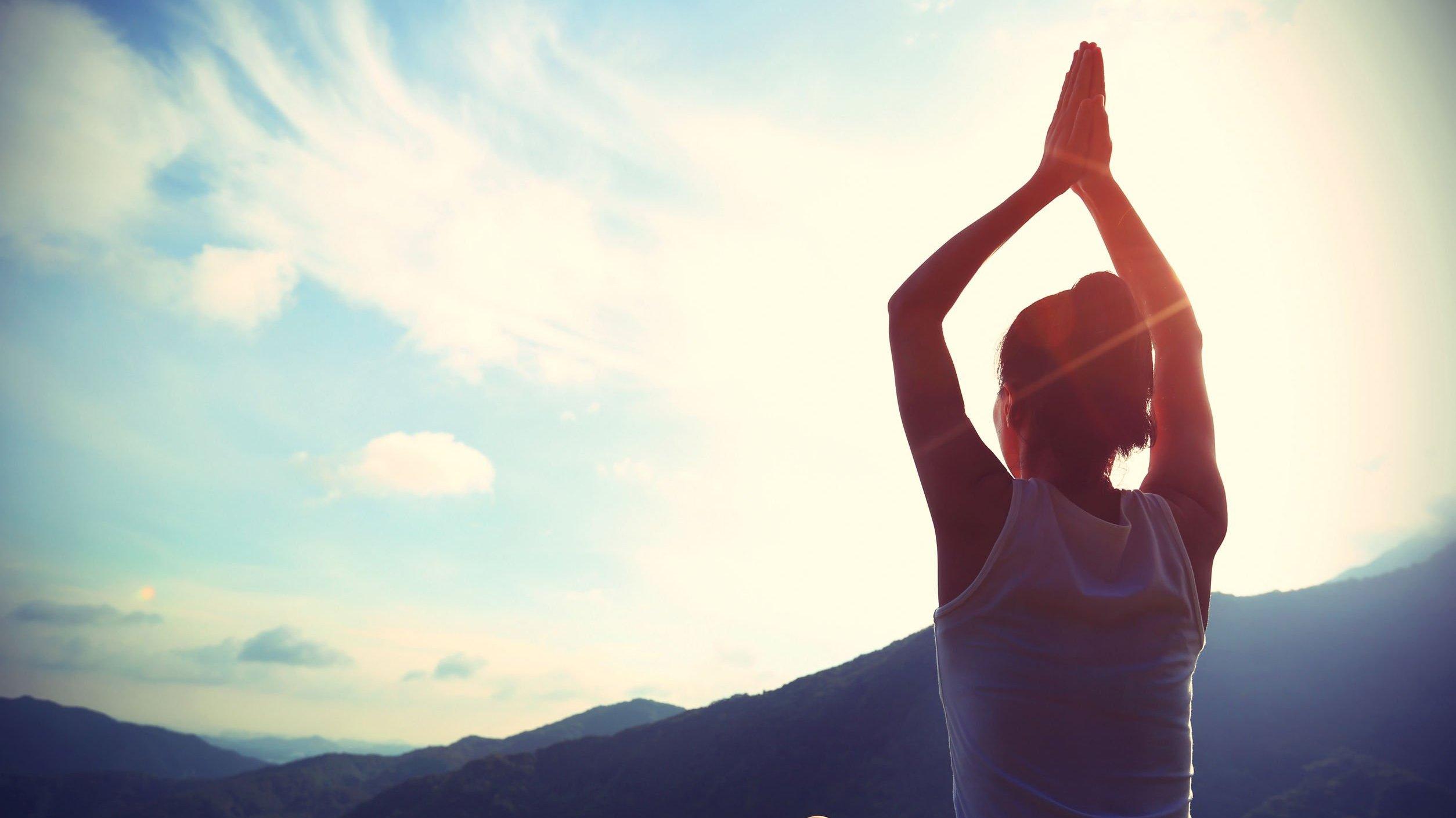Mulher de costas com braços para o alto e mãos unidas no alto e céu azul ao fundo