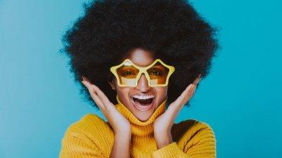 Mulher com blusa de lã e óculos amarelo em formato de estrela, rindo.