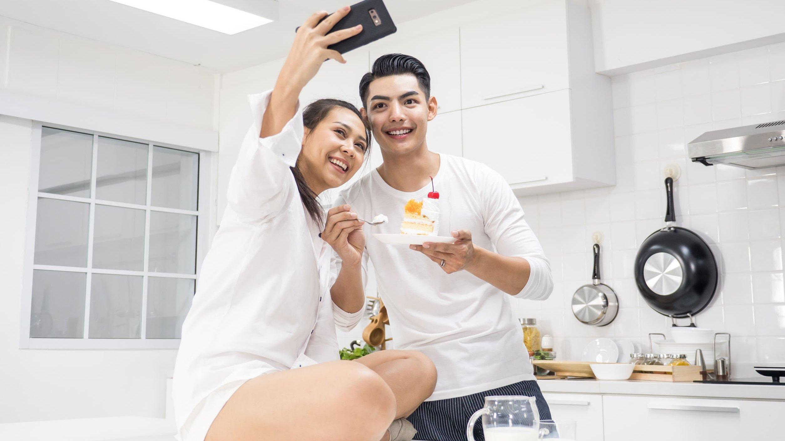 Homem e mulher em casa comendo bolo de aniversário e tirando fotos.