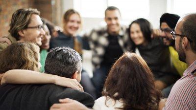 Pessoas em um círculo, com os braços apoiados nas pessoas ao seu lado.