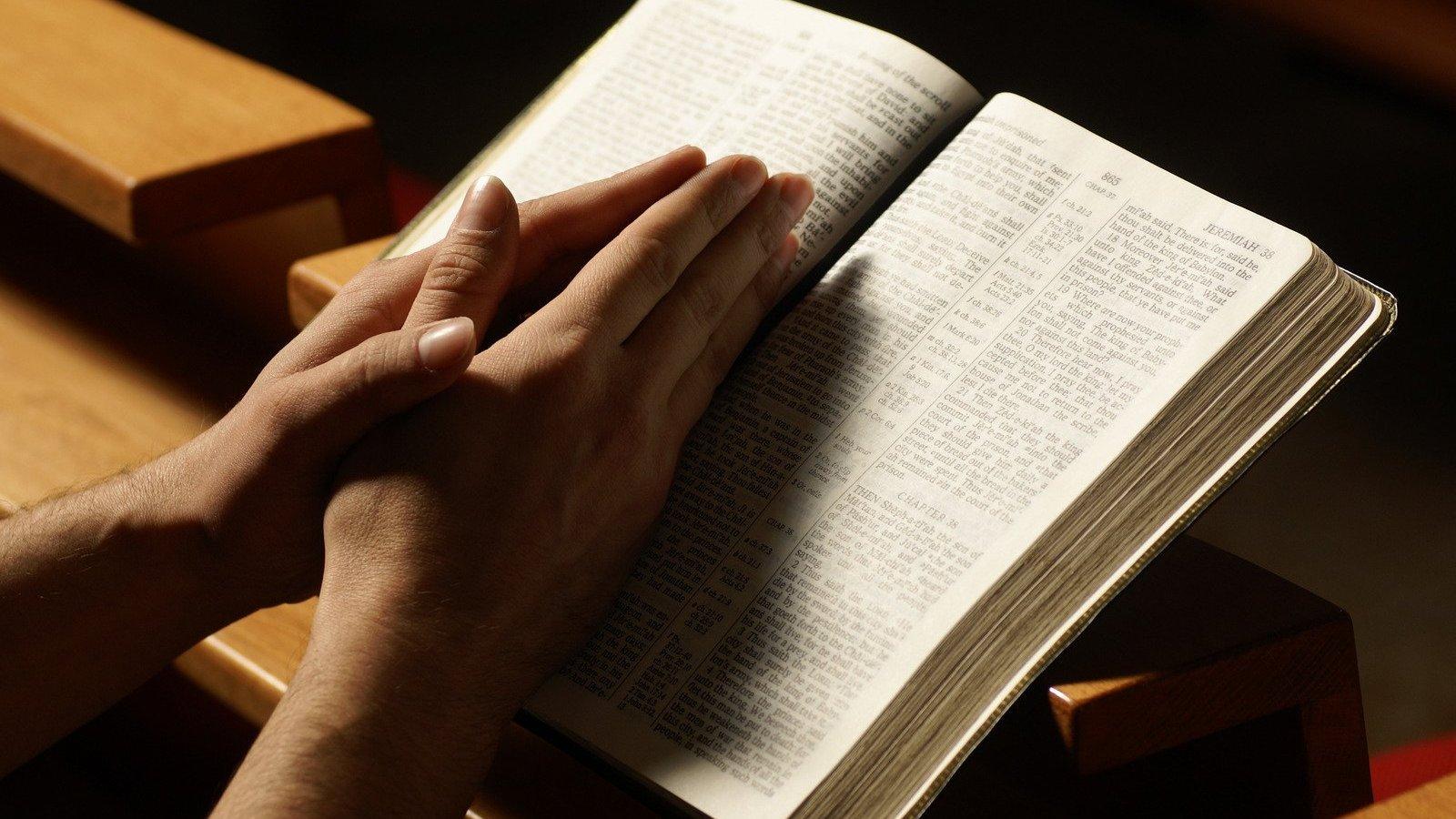 Mãos sobre bíblia.