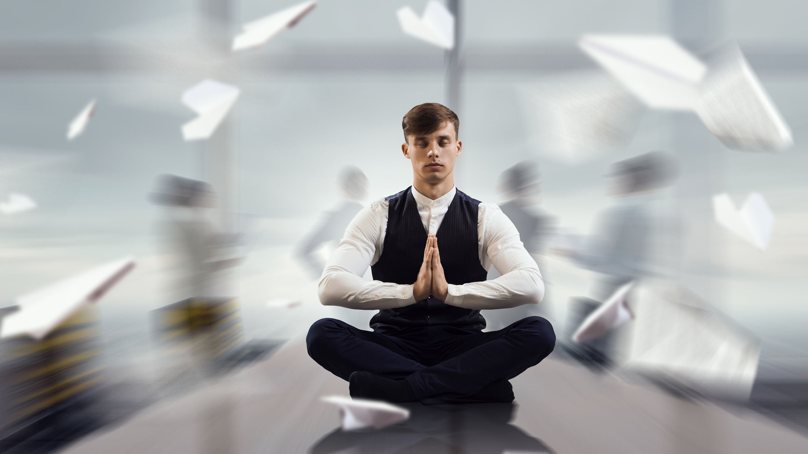 Homem meditando em uma mesa enquanto papeis voam em um escritório