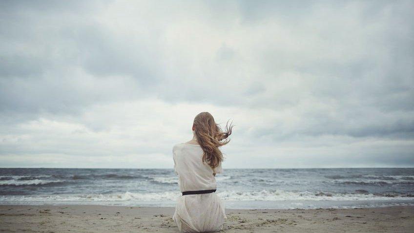 Mulher sentada em areia da praia