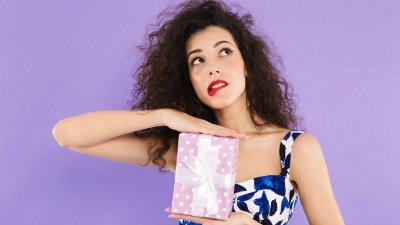 Mulher segurando um presente com expressão com expressão de indecisão.