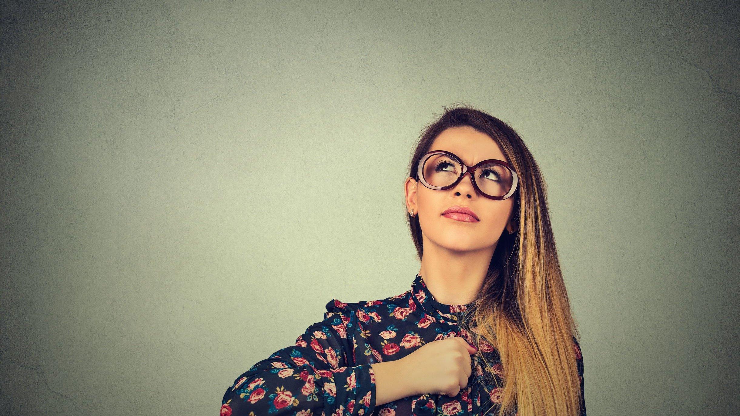 Mulher com óculos e camisa florida com o punho direito fechado no centro de seu peito, e olhando para cima.