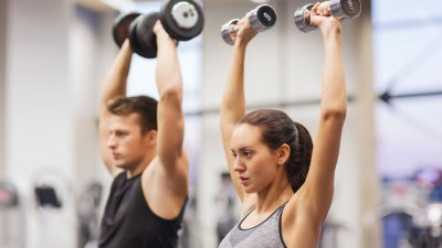 Homem e mulher em academia, levantando pesos. Cada um segura um peso diferente em cada mão.