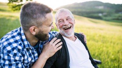 Dois homens sorrindo sentados na grama.