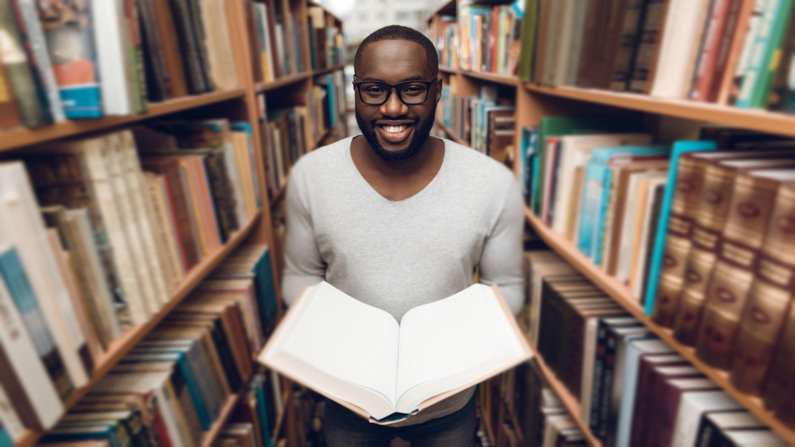 Homem segurando um livro aberto entre prateleiras de biblioteca.