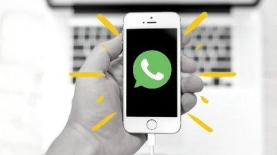 Mão segurando celular em preto e branco e ilustração com logo do whatsapp e luz em volta