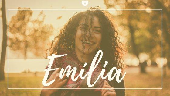 Mulher jovem, de cabelos cacheados, sorrindo, com a palavra Emília escrita em branco