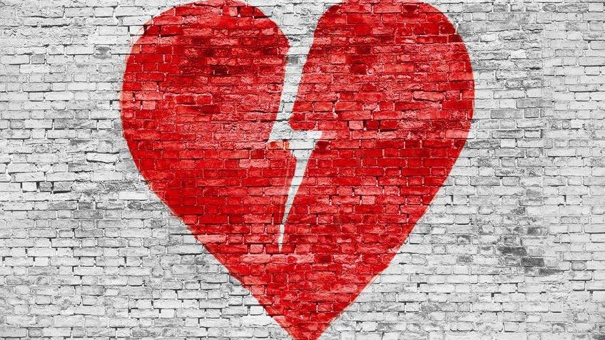 Forma de coração partido pintada na parede de tijolos brancos