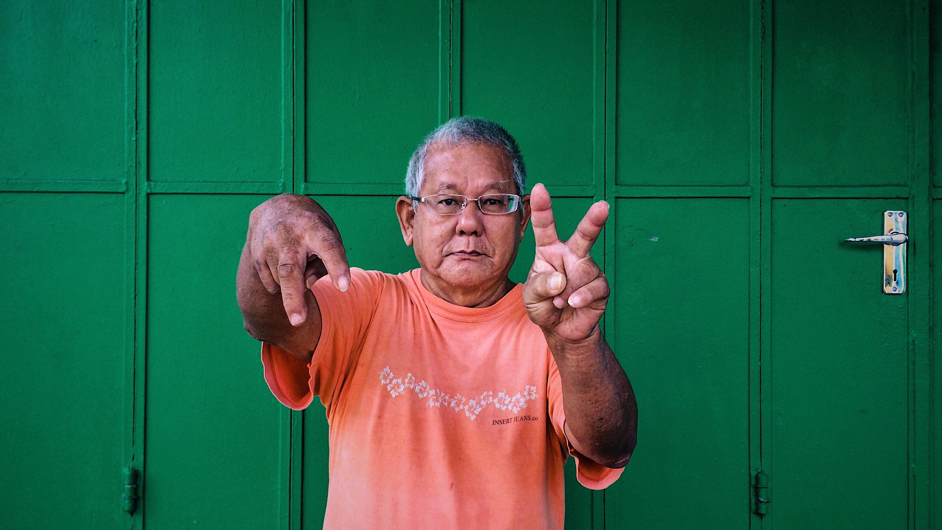 homem fazendo símbolo de paz e amor com as mãos