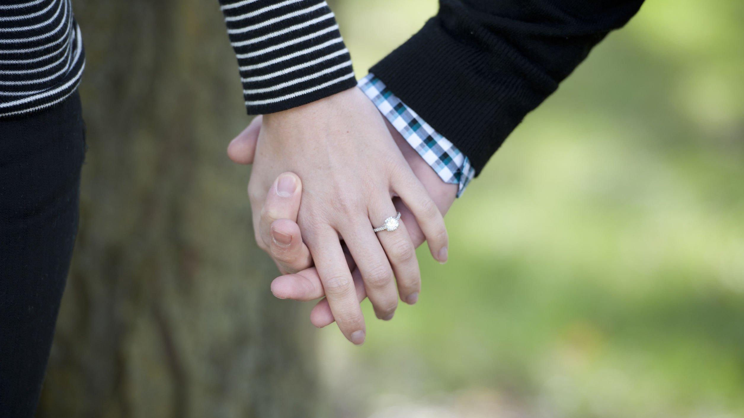 Duas pessoas de mãos dadas, e uma delas usa um anel de noivado.