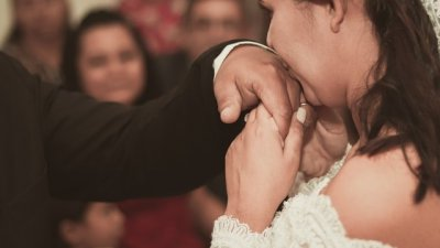 Homem segurando a mão de uma mulher, que usa um anel de noivado, bem próxima ao seu rosto.