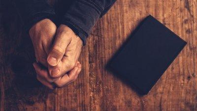 Mãos rezando ao lado de uma bíblia