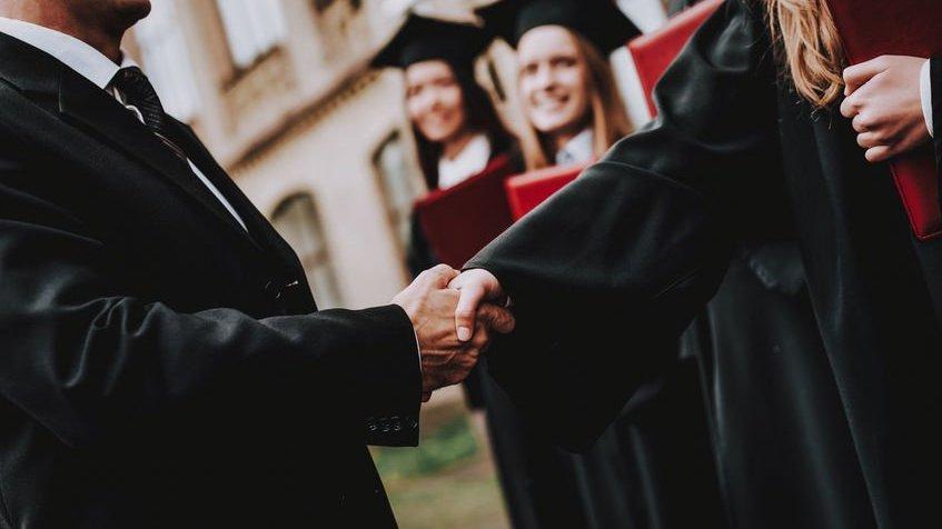 Estudante e docente apertando as mãos