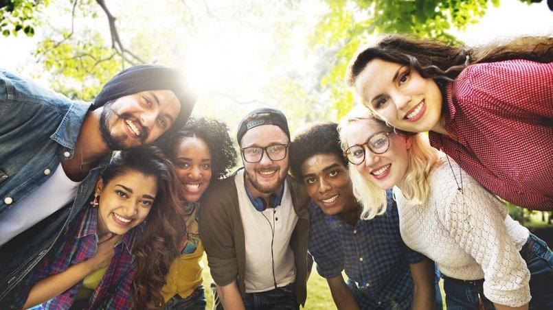 Diversidade de pessoas unidas olhando para foto com árvore ao fundo