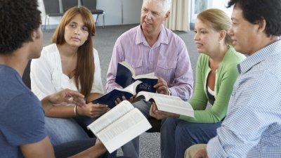 Grupo de pessoas em uma roda, todos com a bíblia na mão.