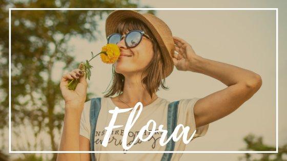 Mulher cheirando flor e sorrindo
