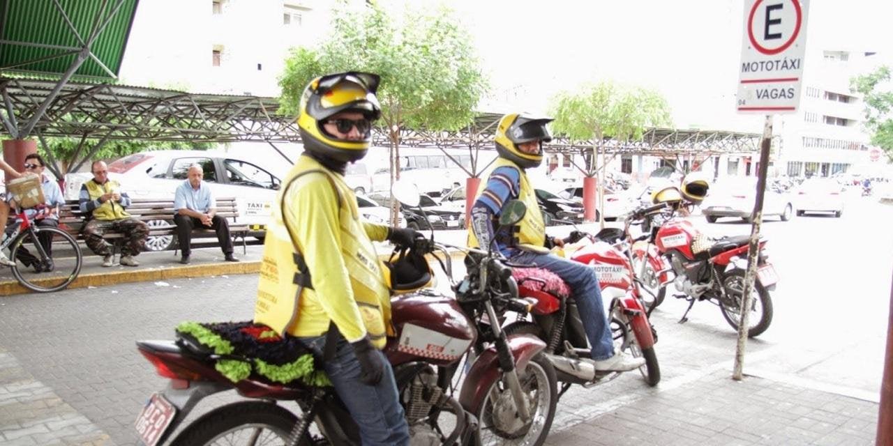 Dois homens vestidos de mototaxistas, sentados em cima de moto na rua