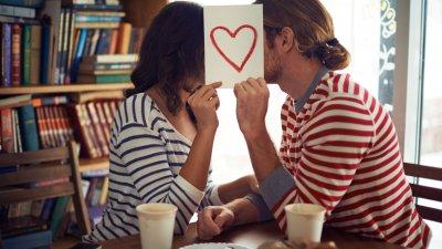 Foto de casal se escondendo atrás de cartão com desenho de coração