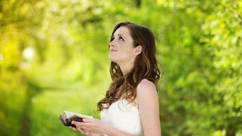 Mulher em pé com bíblia nas mãos olhando para o céu com fundo de folhagem verde